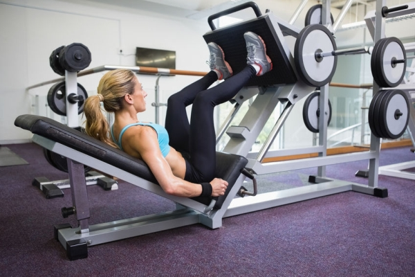 30861788 - side view of a fit young woman doing leg presses in the gym
