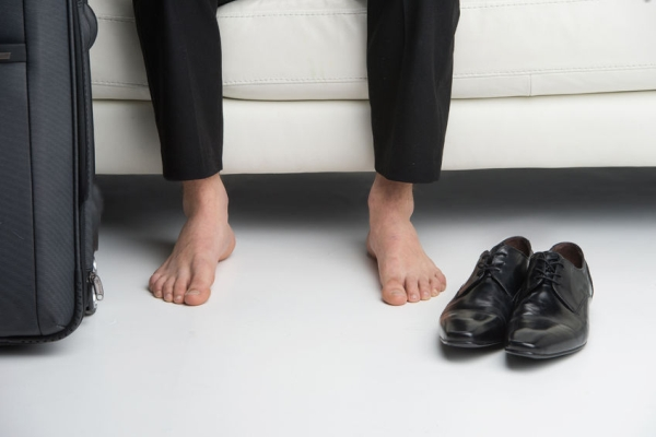 23335178 - close up of bare feet of a business man. having traveling suitcase and shoes near