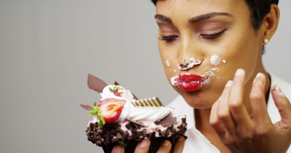 33804035 - black woman making a mess eating a huge fancy dessert