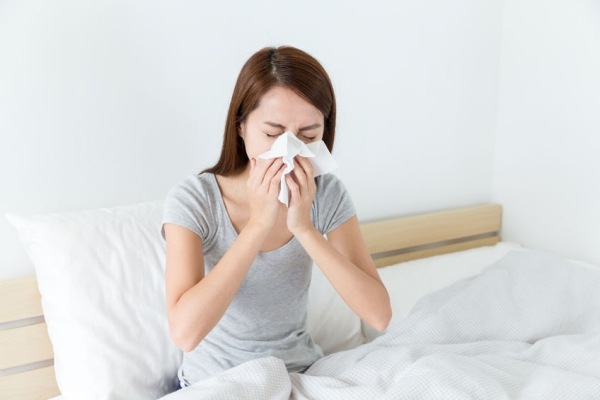 45308066 - asian woman feeling unwell and sneeze on bed