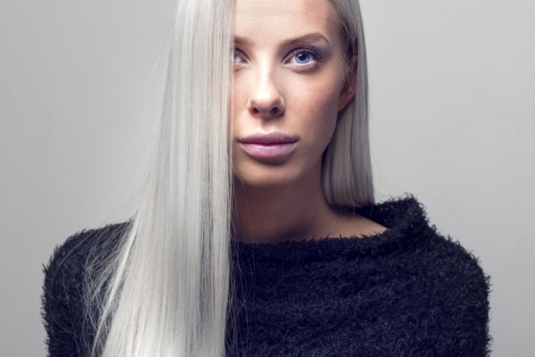 61032300 - beautiful young fashion woman with long blonde hair and black furry design jacket. studio photography. gray backround.