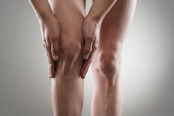 38045885 - female healthy legs. woman touching her injured knee. rheumatism or arthritis concept.