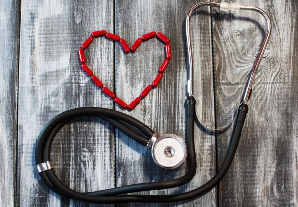 70551869 - the concept of medicine - the stethoscope, red heart on wooden background