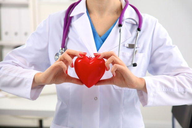 45284251 - young woman doctor holding a red heart, in office.