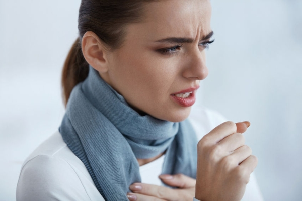 75263420 - woman caught a cold. closeup of beautiful sick female in scarf with strong cough feeling pain in her sore throat. portrait of  unhealthy girl coughing indoors. sickness and illness. high resolution