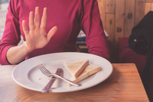 34659140 - a woman on a gluten free diet is saying no thanks to toast