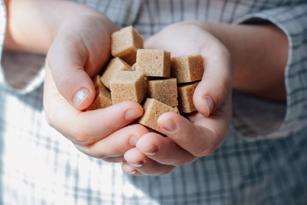89316342 - woman holds brown sugar cubes in hands