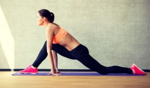 34736044 - fitness, sport, training and lifestyle concept - smiling woman stretching leg on mat in gym
