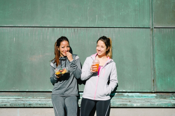 53157172 - sporty women eating healthy food after outdoor fitness workout. fitness diet nutrition with fruit salad and carrot  orange detox smoothie.