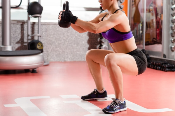 73167610 - woman doing kettlebell weight exercise indoors