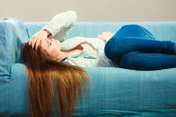 39187279 - loneliness negative emotion concept. young sad stressed woman lying on couch at home