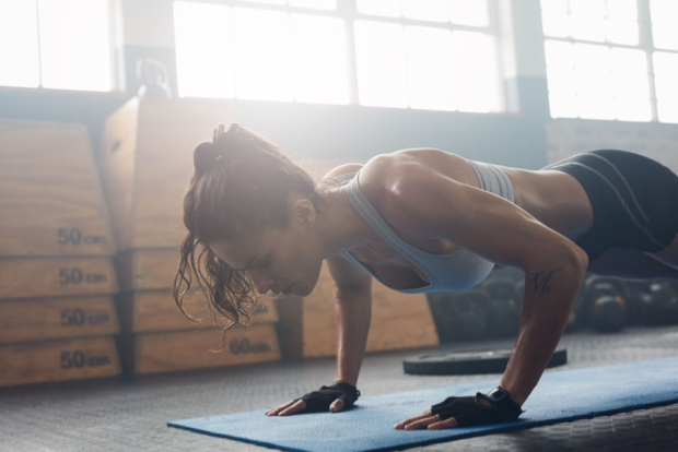 58716600 - shot of young woman doing push-ups at the gym. muscular female doing pushups on exercise mat at gym. female exercising on fitness mat at gym.