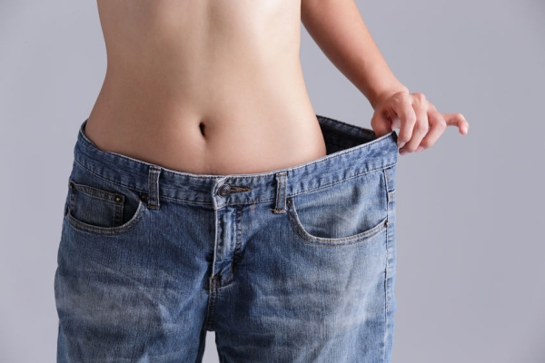 40856233 - woman shows weight loss by wearing old jeans, asian beauty