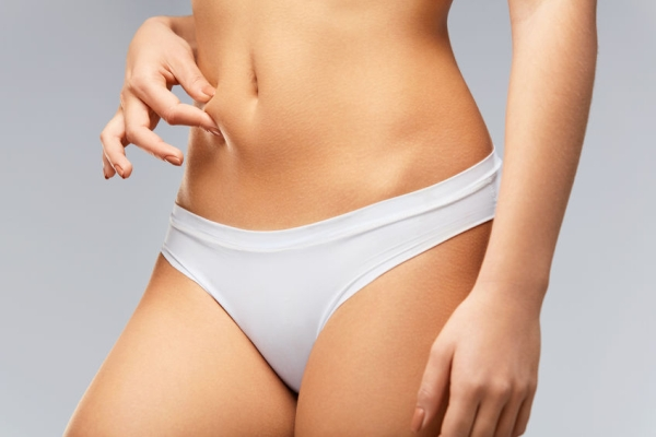 74374471 - beautiful slim woman in perfect body shape. closeup healthy female with soft skin, fit flat belly in bikini panties holding skin with fingers, measuring fat. weight loss diet concept. high resolution