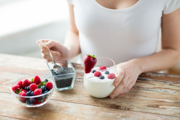 57275984 - healthy eating, vegetarian food, diet and people concept - close up of woman hands with yogurt, berries and poppy or chia seeds on spoon