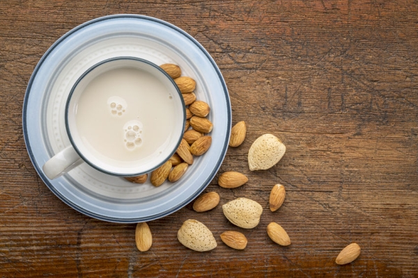 35208370 - a cup of almond milk with almond nuts on a rustic barn wood table