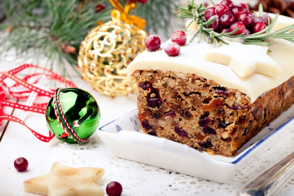 47340510 - traditional christmas fruit cake pudding with marzipan and cranberry and rosemary decor on a christmas decoration background