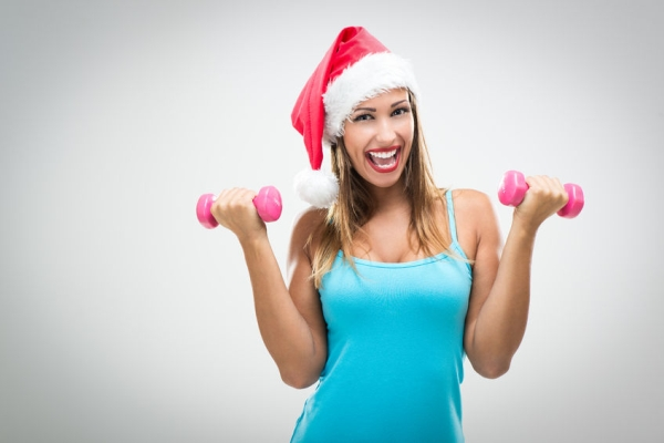 47197707 - beautiful fitness woman wearing santa hat doing exercise training arms lifting dumbbells.