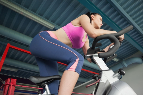 25787253 - low angle view of a determined young woman working out at spinning class in gym