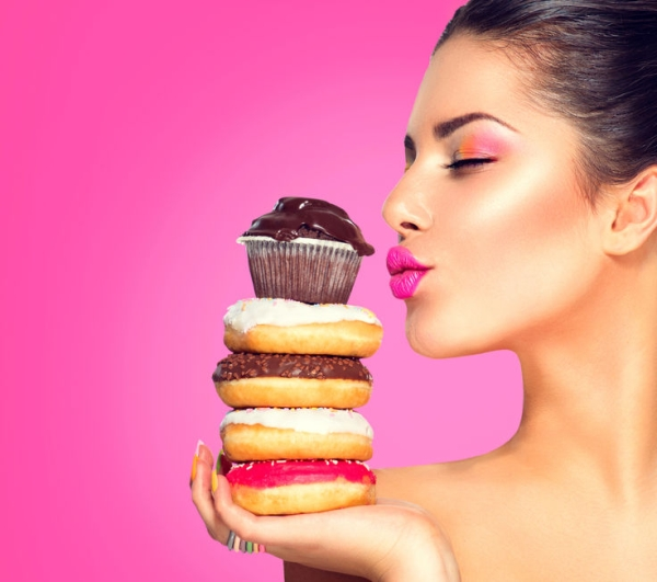 36897636 - beauty fashion model girl taking sweets and colorful donuts