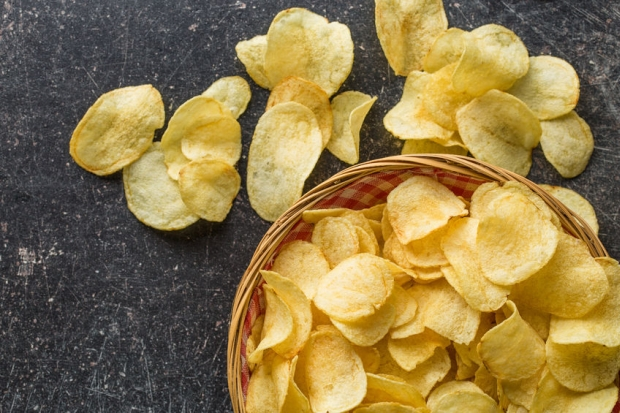 55312346 - crispy potato chips in a wicker bowl on old kitchen table