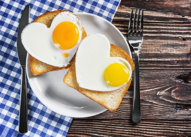 44714650 - two toast with scrambled eggs in the shape of a heart on a plate