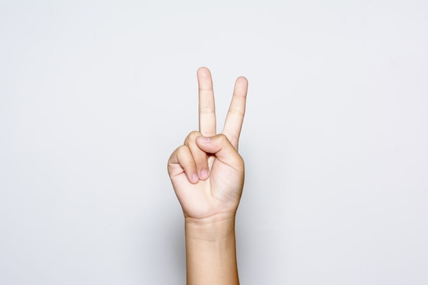 42598798 - boy raising two fingers up on hand it is shows peace strength fight or victory symbol and letter v in sign language on white background.