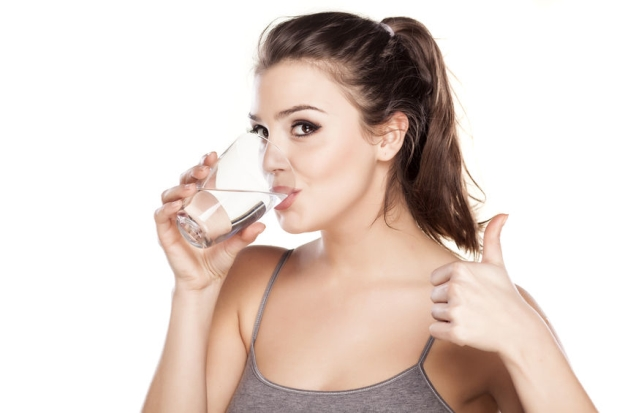 47458537 - beautiful woman drinks water from a glass and showing thumb up