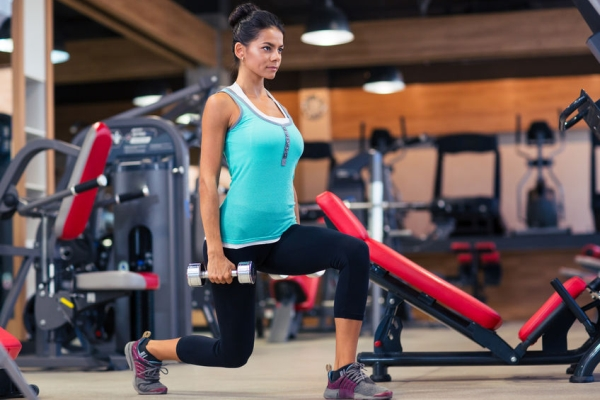 44255932 - full length portrait of a young woman workout with dumbbells in fitness gym