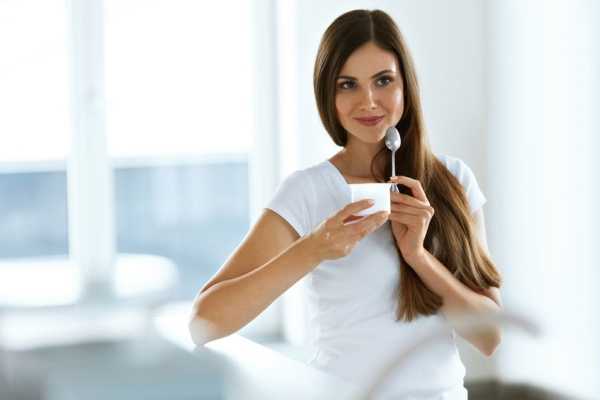 68361800 - healthy lifestyle. portrait of beautiful sexy smiling woman tasting fresh organic yogurt. charming cheerful girl on diet nutrition eating delicious natural yoghurt, dairy food. high resolution