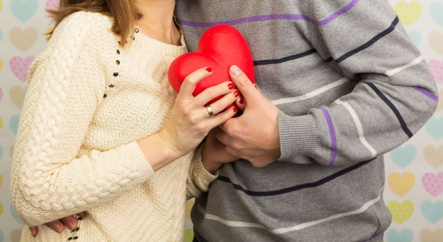 35446082 - a couple in love holding red heart