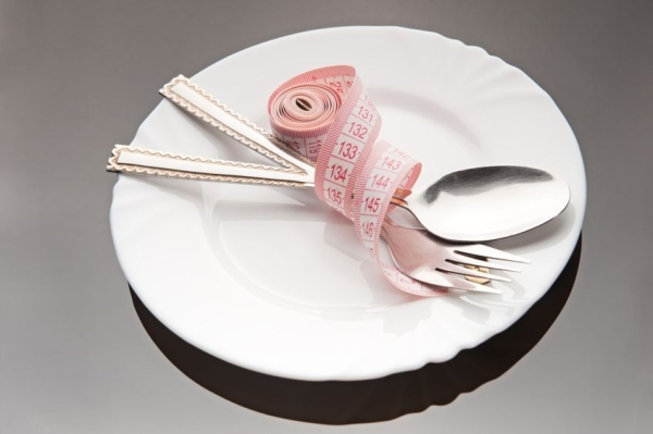 12876122 - empty plate with a spoon, fork and measuring tape