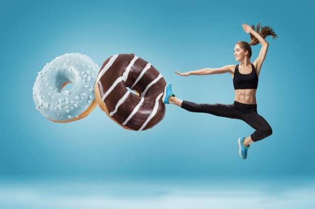 55035269 - fit young woman fighting off bad food on a  blue background. concept of diet and healthy lifestile