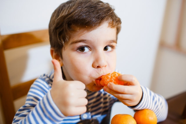 51792779 - 4-years boy eat a mandarin and show up his big finger
