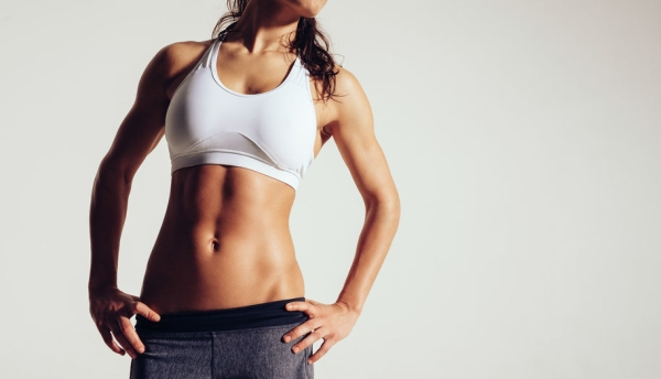 37358281 - close up of fit woman's torso with her hands on hips. female with perfect abdomen muscles on grey background with copyspace.
