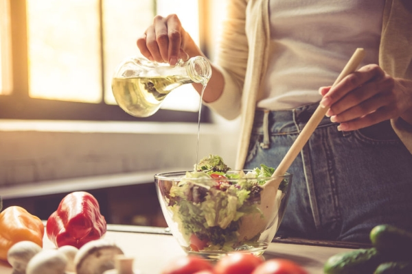 64347318 - cropped image of beautiful young girl mixing salad while cooking in kitchen at home