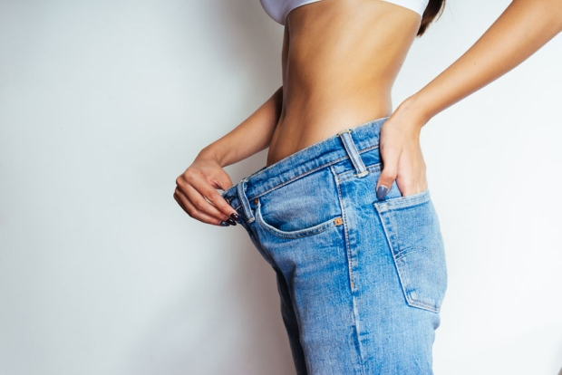88133182 - a slender girl shows how much she lost weight, jeans have become big