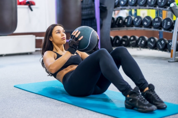 48565557 - work out fitness woman doing sit ups abs abdominal crunches core exercises with medecine ball