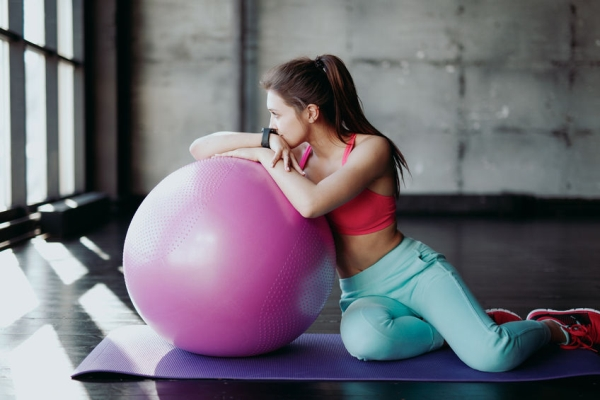 79149497 - fitness, sport, training and people concept - smiling woman flexing abdominal muscles with exercise ball in gym