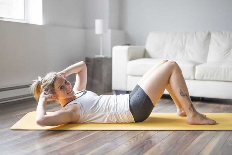 86442912 - full length portrait of attractive young woman working out at home in living room, doing yoga or pilates exercise