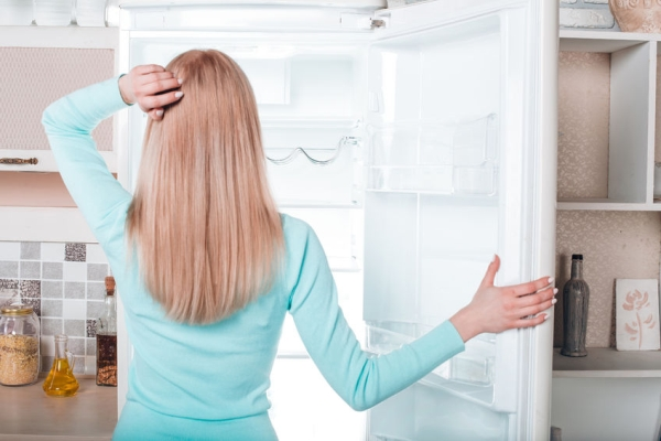 55581964 - what's for dinner? pretty blonde standing near open empty fridge. back view photo of thoughtful young woman. she looking at fridge