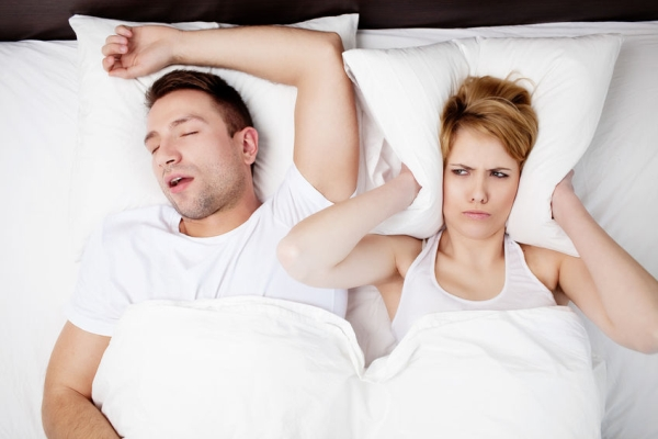 53952995 - snoring man and young woman. couple sleeping in bed.