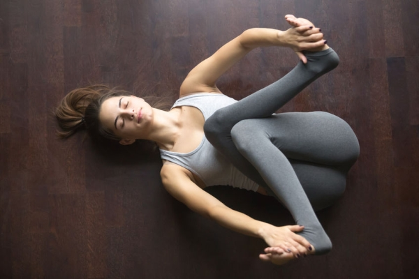 68916136 - beautiful young model working out at home, doing yoga exercise on floor, lying in supta gomukhanasa reclined cowface pose , posture for sciatica, resting after practice. full length, high angle view