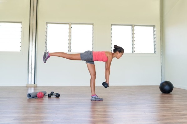 65604143 - woman strength training at gym exercising hamstring and lower back muscles with single-leg romanian deadlift exercicses with free weights dumbbells. asian girl alone indoors in fitness center room.