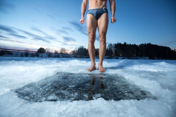 35423451 - young man standing by ice hole and ready to swim in the winter water
