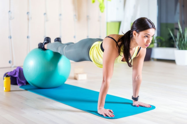 48565370 - woman doing pilates exercises with fit ball in gym or yoga class