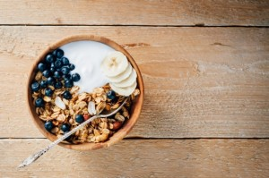 46624652 - homemade oatmeal granola with peanuts, blueberry and banana in wooden bowl, sunny morning