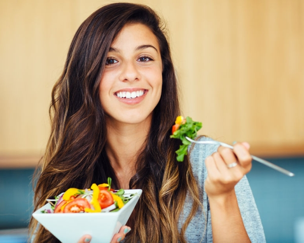 26326571 - attractive young woman eating salad