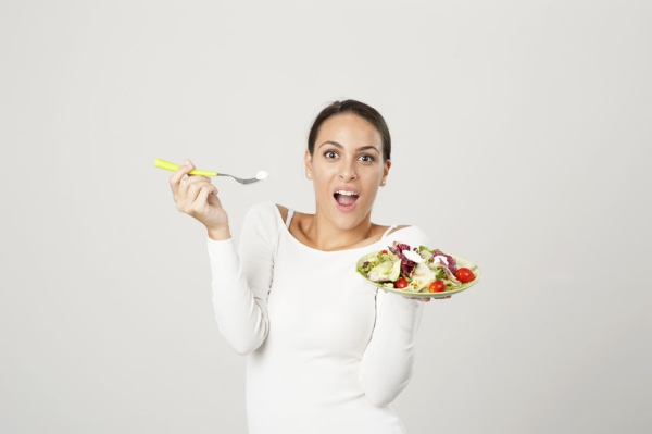 45567730 - woman eating salad against a white background