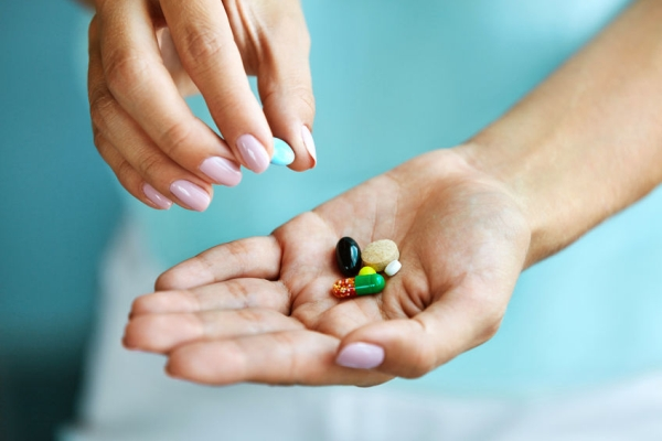 69595991 - vitamins and supplements. closeup of female hand holding variety of colorful pills on palm. close-up of woman fingers taking medication tablets, capsules from hand. medicine concept. high resolution